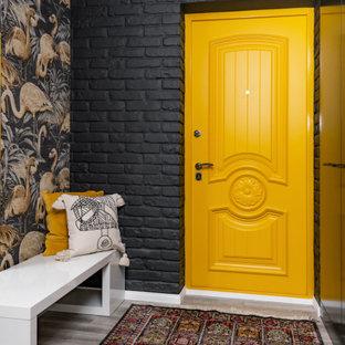 На фото: узкая прихожая среднего размера в современном стиле с черными стенами, одностворчатой входной дверью, желтой входной дверью, серым полом и кирпичными стенами с