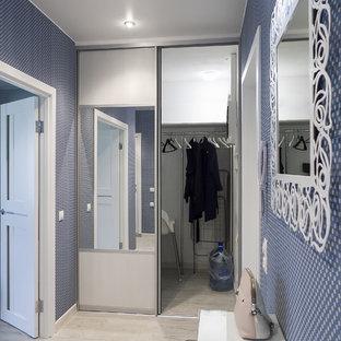 Réalisation d'une porte d'entrée design de taille moyenne avec un mur bleu, un sol en vinyl, une porte pivot, une porte blanche, un sol gris et du papier peint.