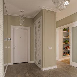 На фото: входная дверь со шкафом для обуви в современном стиле с бежевыми стенами, одностворчатой входной дверью, белой входной дверью и коричневым полом