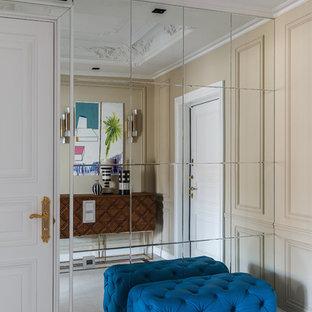 На фото: прихожая в стиле неоклассика (современная классика) с бежевыми стенами, белым полом и одностворчатой входной дверью с