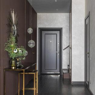 На фото: узкая прихожая в современном стиле с темным паркетным полом, одностворчатой входной дверью, черной входной дверью и коричневыми стенами с