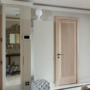 Пример оригинального дизайна: узкая прихожая среднего размера в стиле неоклассика (современная классика) с серыми стенами, полом из травертина, одностворчатой входной дверью, бежевым полом и входной дверью из светлого дерева