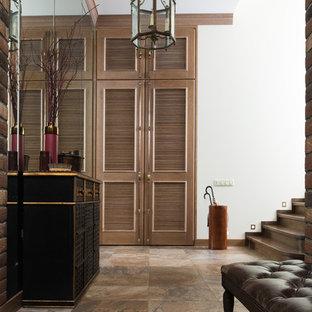 На фото: прихожая в стиле современная классика с белыми стенами и коричневым полом с