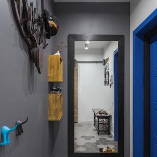 Modelo de puerta principal nórdica, pequeña, con paredes grises, suelo de baldosas de porcelana, puerta simple, puerta azul y suelo gris