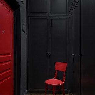Idée de décoration pour une entrée urbaine de taille moyenne avec un couloir, un mur noir, sol en stratifié, une porte simple, une porte rouge et un sol marron.
