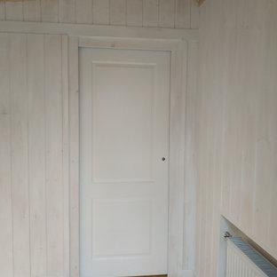 Exemple d'une petit porte d'entrée scandinave avec un mur blanc, un sol en bois peint, une porte coulissante et une porte blanche.
