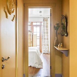 Стильный дизайн: маленькая узкая прихожая в стиле фьюжн с желтыми стенами, мраморным полом, коричневым полом, одностворчатой входной дверью и правильным освещением - последний тренд