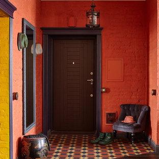 Modelo de distribuidor bohemio, de tamaño medio, con paredes rojas, suelo de baldosas de cerámica, puerta simple, puerta de madera oscura y suelo multicolor