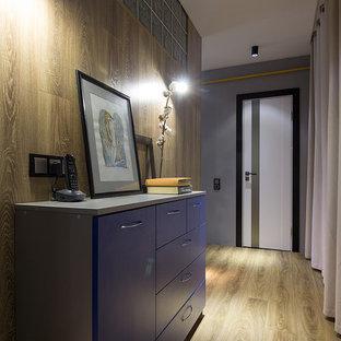 Exempel på en mellanstor industriell hall, med grå väggar, laminatgolv, en enkeldörr, en gul dörr och beiget golv