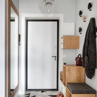 На фото: узкая прихожая в скандинавском стиле с серыми стенами, одностворчатой входной дверью, белой входной дверью и разноцветным полом с