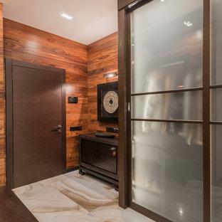 Неиссякаемый источник вдохновения для домашнего уюта: большая прихожая в современном стиле с полом из керамогранита, одностворчатой входной дверью, входной дверью из темного дерева и коричневыми стенами