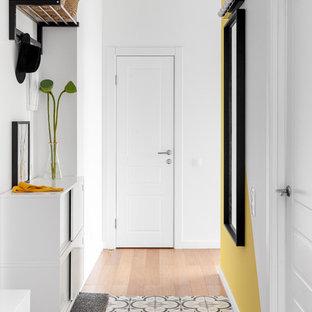 Inredning av en minimalistisk hall, med vita väggar, klinkergolv i keramik, en enkeldörr, en vit dörr och flerfärgat golv