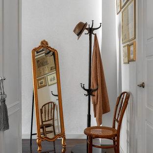Ejemplo de entrada clásica renovada con paredes blancas, suelo de madera en tonos medios y suelo marrón