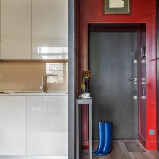 Свежая идея для дизайна: входная дверь в современном стиле с красными стенами, паркетным полом среднего тона, одностворчатой входной дверью, черной входной дверью и коричневым полом - отличное фото интерьера