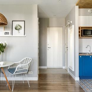 Свежая идея для дизайна: входная дверь в скандинавском стиле с серыми стенами, одностворчатой входной дверью, белой входной дверью, паркетным полом среднего тона и коричневым полом - отличное фото интерьера