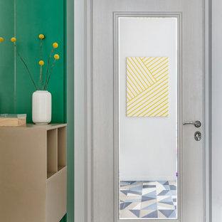 Cette image montre une entrée nordique de taille moyenne avec un couloir, un mur gris, un sol en carrelage de céramique, une porte simple, une porte en bois clair et un sol bleu.