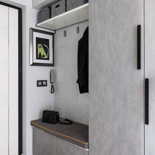 Стильный дизайн: маленький тамбур в современном стиле с серыми стенами, одностворчатой входной дверью, белой входной дверью и бежевым полом - последний тренд