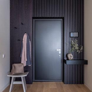 На фото: входная дверь в современном стиле с черными стенами, паркетным полом среднего тона, одностворчатой входной дверью, черной входной дверью и коричневым полом