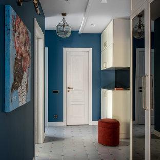 Неиссякаемый источник вдохновения для домашнего уюта: маленькая узкая прихожая в современном стиле с синими стенами, полом из керамической плитки, разноцветным полом, одностворчатой входной дверью и белой входной дверью