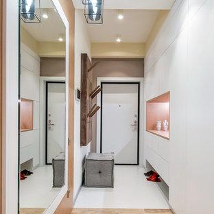 На фото: входная дверь в современном стиле с одностворчатой входной дверью, белой входной дверью, белыми стенами и белым полом с