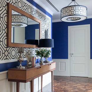 Свежая идея для дизайна: входная дверь в стиле современная классика с синими стенами, одностворчатой входной дверью, белой входной дверью и коричневым полом - отличное фото интерьера