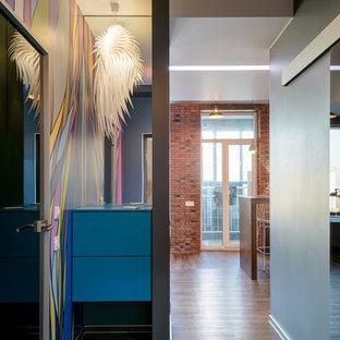 Пример оригинального дизайна: входная дверь в современном стиле с разноцветными стенами, полом из ламината, коричневым полом, одностворчатой входной дверью и черной входной дверью