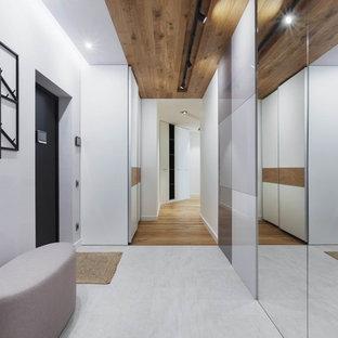 Пример оригинального дизайна интерьера: входная дверь среднего размера в современном стиле с белыми стенами, полом из керамогранита, одностворчатой входной дверью, черной входной дверью и серым полом
