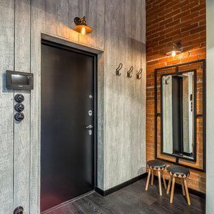 Cette image montre un hall d'entrée urbain avec un mur multicolore, un sol en bois foncé, une porte simple et une porte noire.