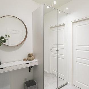 На фото: прихожие среднего размера в скандинавском стиле с белыми стенами, серым полом, полом из керамогранита, одностворчатой входной дверью и серой входной дверью