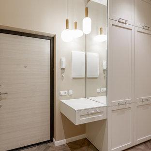 Стильный дизайн: входная дверь в современном стиле с бежевыми стенами, одностворчатой входной дверью, входной дверью из светлого дерева и коричневым полом - последний тренд