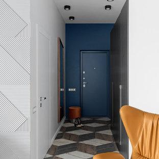 На фото: узкая прихожая среднего размера в современном стиле с белыми стенами, одностворчатой входной дверью, синей входной дверью и разноцветным полом