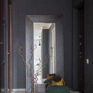 Modern inredning av en hall, med svarta väggar, en enkeldörr, en svart dörr och beiget golv
