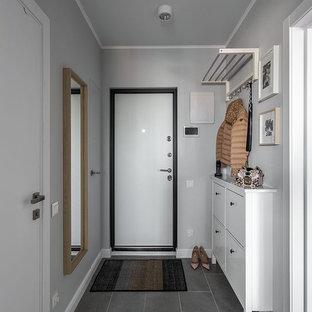 Неиссякаемый источник вдохновения для домашнего уюта: входная дверь в скандинавском стиле с белыми стенами, одностворчатой входной дверью, белой входной дверью и серым полом