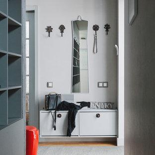 Свежая идея для дизайна: прихожая в современном стиле с белыми стенами, паркетным полом среднего тона и коричневым полом - отличное фото интерьера