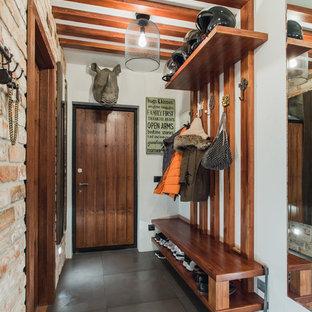 Ejemplo de puerta principal ecléctica con paredes blancas, puerta simple, puerta de madera en tonos medios y suelo gris