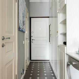 На фото: входные двери в классическом стиле с серыми стенами, одностворчатой входной дверью и белой входной дверью