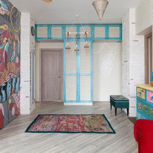 На фото: прихожая в стиле фьюжн с разноцветными стенами, одностворчатой входной дверью, входной дверью из дерева среднего тона и серым полом с