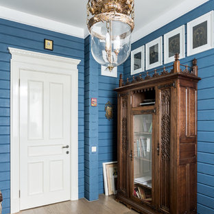 Réalisation d'une entrée champêtre avec un mur bleu, un sol en bois clair et un sol beige.