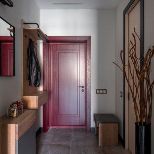 Cette image montre une porte d'entrée design avec un mur blanc, une porte simple, une porte rouge et un sol gris.