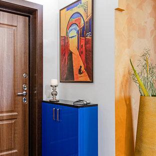 Cette photo montre une porte d'entrée éclectique avec un mur blanc, une porte simple, une porte en bois brun et un sol bleu.