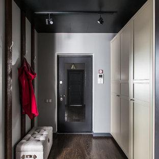 Новые идеи обустройства дома: входная дверь в современном стиле с серыми стенами, темным паркетным полом, одностворчатой входной дверью, черной входной дверью и коричневым полом