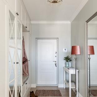 Modelo de puerta principal clásica, pequeña, con paredes verdes, suelo laminado, puerta simple, puerta blanca y suelo beige