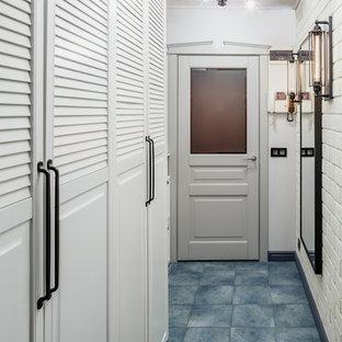На фото: маленькая узкая прихожая в стиле лофт с серыми стенами, полом из керамогранита и синим полом