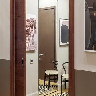 Modern inredning av ett litet kapprum, med grå väggar, mellanmörkt trägolv, en skjutdörr, mellanmörk trädörr och gult golv