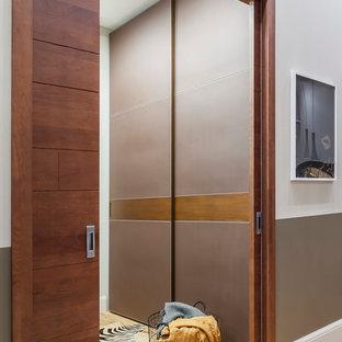 Exempel på ett litet modernt kapprum, med grå väggar, mellanmörkt trägolv, en skjutdörr, mellanmörk trädörr och gult golv