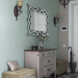 Стильный дизайн: узкая прихожая в стиле современная классика с зелеными стенами, полом из керамогранита и серым полом - последний тренд
