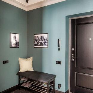 Réalisation d'une porte d'entrée tradition de taille moyenne avec un mur bleu, une porte simple, une porte noire, un sol en carrelage de porcelaine et un sol noir.