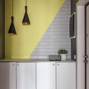 На фото: прихожая в скандинавском стиле с желтыми стенами, одностворчатой входной дверью, белой входной дверью и коричневым полом с