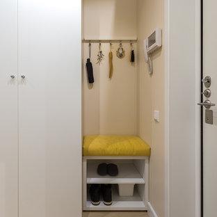 Modelo de puerta principal nórdica, pequeña, con paredes beige, suelo de madera clara, puerta simple, puerta blanca y suelo beige