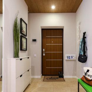 Свежая идея для дизайна: маленькая входная дверь в современном стиле с белыми стенами, полом из керамогранита, одностворчатой входной дверью, входной дверью из дерева среднего тона и бежевым полом - отличное фото интерьера
